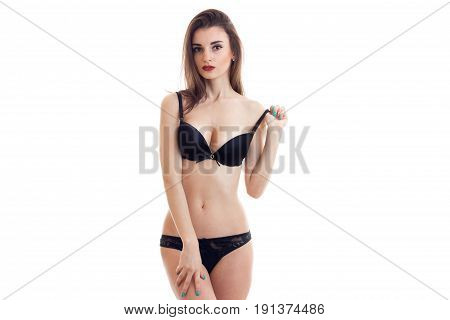 Slim sexy girl stands in front of the camera in lingerie and erotic keeps the ball from tulle bra isolated on white background
