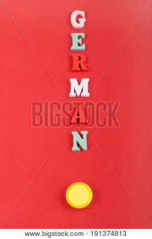 German word on red background composed from colorful abc alphabet block wooden letters, copy space for ad text. Learning english concept