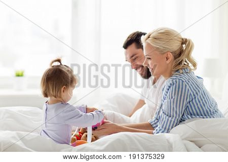 people, family, holidays and morning concept - happy little girl and parents with gift box in bed at home