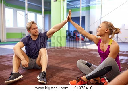fitness, sport, exercising, gesture and people concept - happy couple resting and making high five in gym