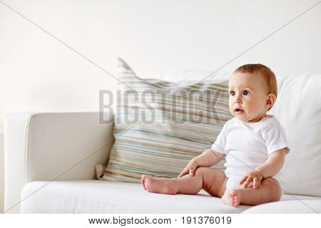 childhood, babyhood and people concept - happy little baby boy or girl sitting on sofa at home