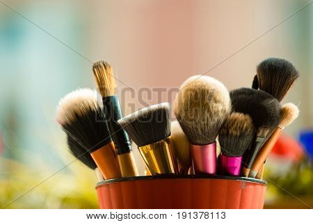 fashion brush for fashionable makeup or cosmetic in pink cup on blurred background beauty visage and design