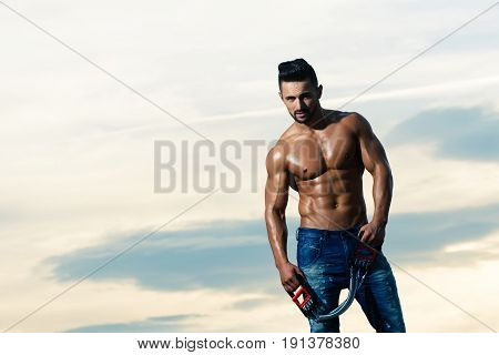 Sexy Man With Muscular Body Workout With Expander Gripper