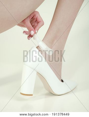 wound on leg. adhesive plaster on female leg with wound in fashionable shoes young girl isolated on white background skincare and health