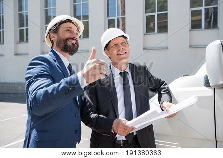 Two Smiling Architects In Hardhats Holding Blueprint And Showing Thumb Up