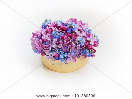 Petite, small bouquet of purple lilacs and the blue forget-me-nots on a white background