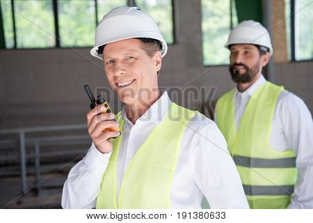 Smiling Mature Constructor In Professional Equipment Talking On Radio Set