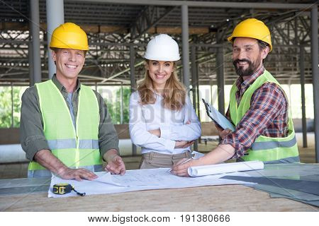 Middle Aged Constructors And Contractor Looking At Camera During Work On Construction Site