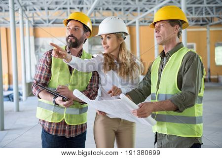 Mature Builders And Contractor Talking During Work On Construction Site