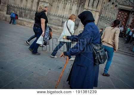 Barcelona Spain - October 27 2015: Homeless woman begs for money from tourists visiting Barcelona Cathedral.