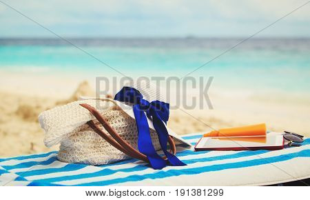 bag, suncream, glasses and touch pad on tropical beach