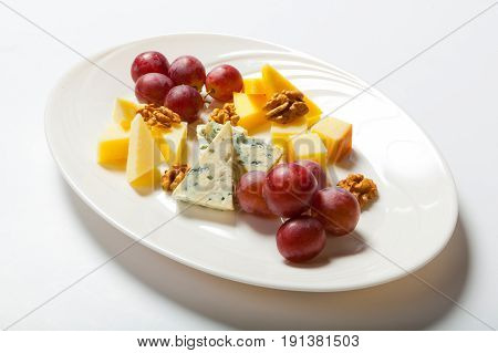 Cheese And Nuts, And Grapes On The White Plate