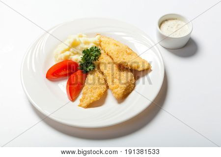 Fish In Breadcrumbs With Garlic Sauce On The White Background