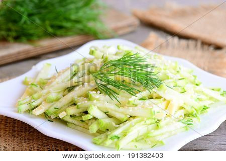 Raw zucchini and cheese salad with lemon vinaigrette. Light salad with raw zucchini, cheese, sesame seeds and dill on a white plate. Tasty and quick vegetarian salad. Rustic style. Closeup