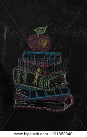 Stack of books with apple drawn with chalk on blackboard. Education, school concept