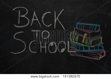 Back to school text and stack of books with apple drawn with chalk on blackboard. Education, school concept