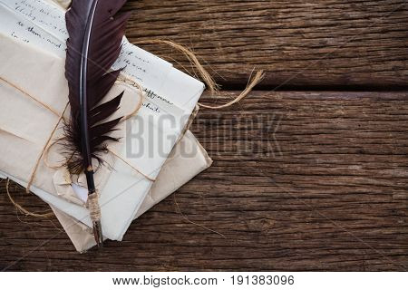 Quill feather with nostalgic letters on wooden table