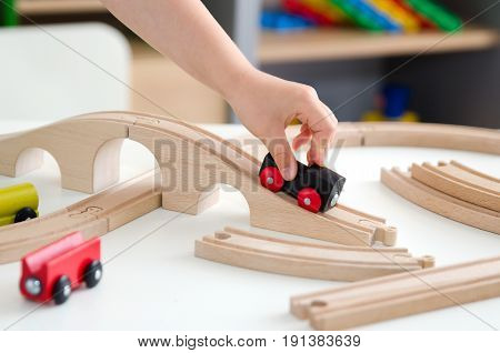 Child plays with a wooden toy train. toy wooden train toys education white background wood concept