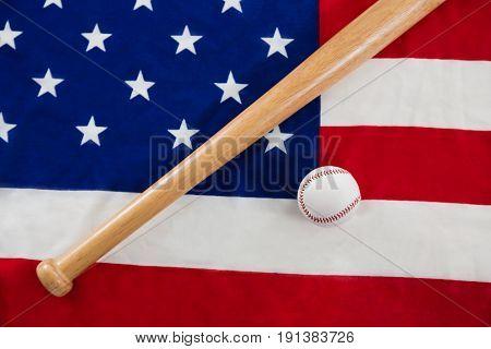 Close-up of baseball and baseball bat on an American flag