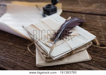 Quill feather with legal documents arranged on wooden table