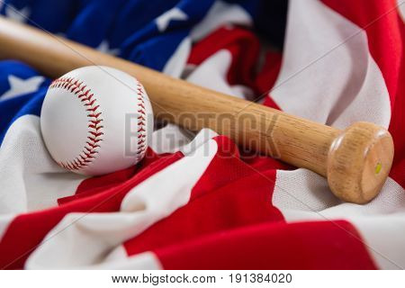 Close-up of baseball and baseball bat on an American flag