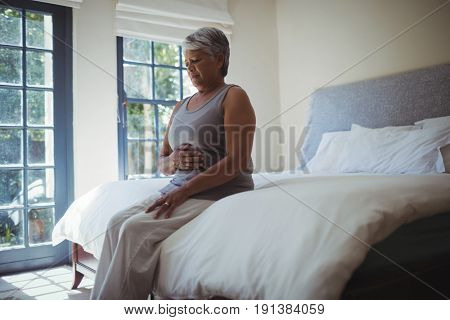 Upset senior woman touching belly on bed at home