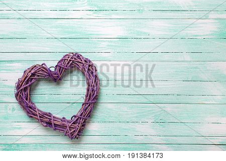 Decorative heart on turquoise wooden background. Top view. Place for text.