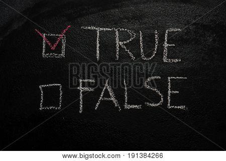 True or False written with white chalk on blackboard