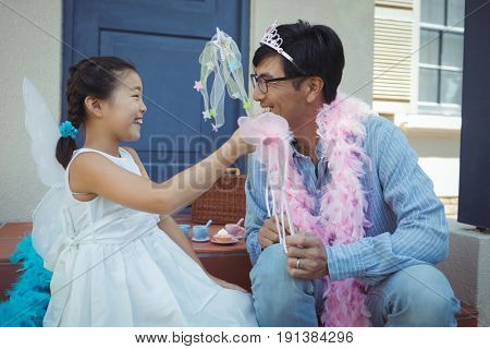 Father and daughter in fairy costume at home
