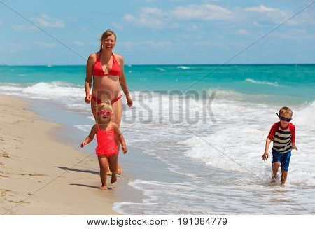 happy pregnant mother with kids play on tropical beach