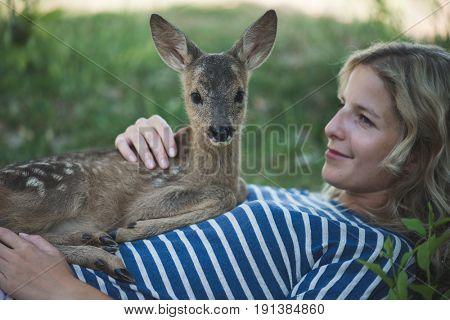 Cute roe deer lying on human