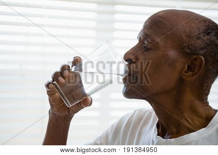 Senior man drinking water against window in bathroom at home