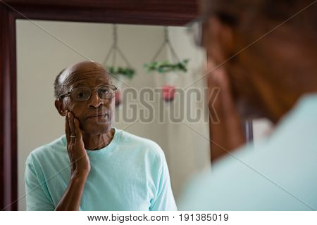 Concerned senior man rubbing cheek while looking into mirror in bathroom