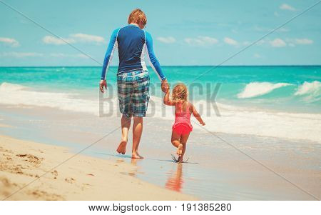 father with little daughter walk on tropical beach