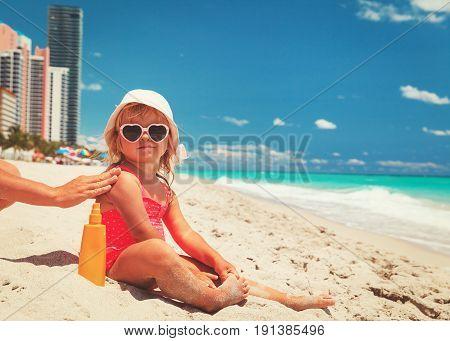 mother applying sunblock cream on daughter shoulder on beach