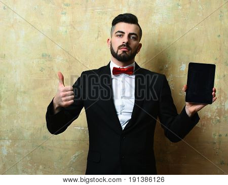 Man of business with beard confident face expression and stylish outfit holds high tech tablet and shows thumbs up on old beige wall background. Concept of modern business approach
