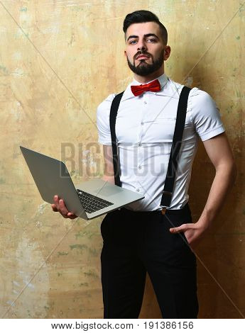 Man with beard in white shirt and bow tie with confident face expression holds laptop in one hand and puts another hand in pocket on beige background. Concept of career and professionalism
