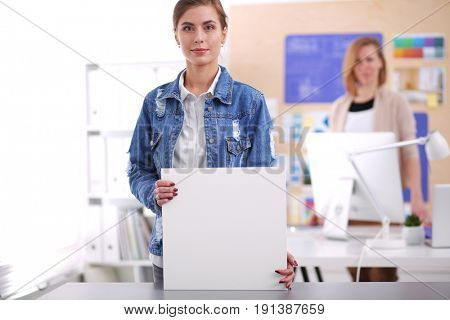 Two young woman standing near desk with instruments, plan and la