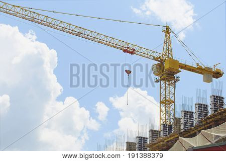Construction crane against the blue sky, Construction crane on a background of beautiful blue sky with clouds