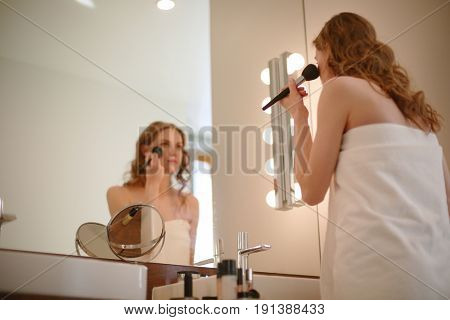 Young woman looking in the mirror and putting make-up on.