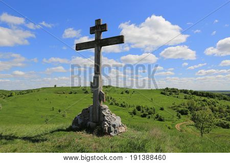 Cross on green hill in sunny day