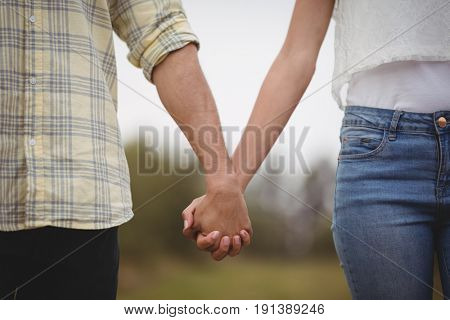 Mid section of couple holding hands while standing at farm