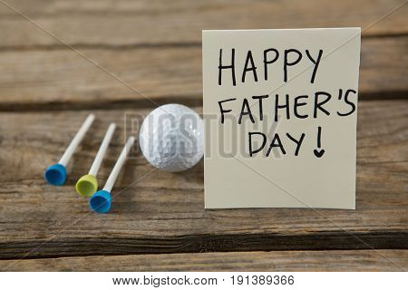 Close up of greeting card with happy fathers day text by golf ball and tees on wooden table
