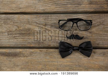 Overhead view of bow tie with mustache and eyeglasses on wooden table