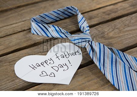 Close up of heart shape paper with text by necktie on wooden table