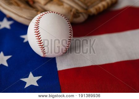 Close-up of baseball and gloves on an American flag