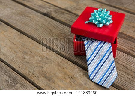 High angle view of necktie in red gift box on wooden table
