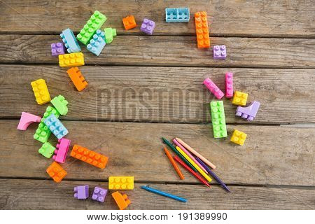 Overhead view of toy blocks with crayons on wooden table