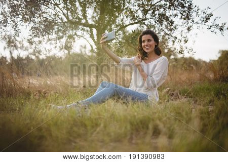 Beautiful young woman taking selfie while sitting on grassy field at farm
