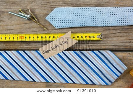 Overhead view of text with neckties and work tools on wooden table
